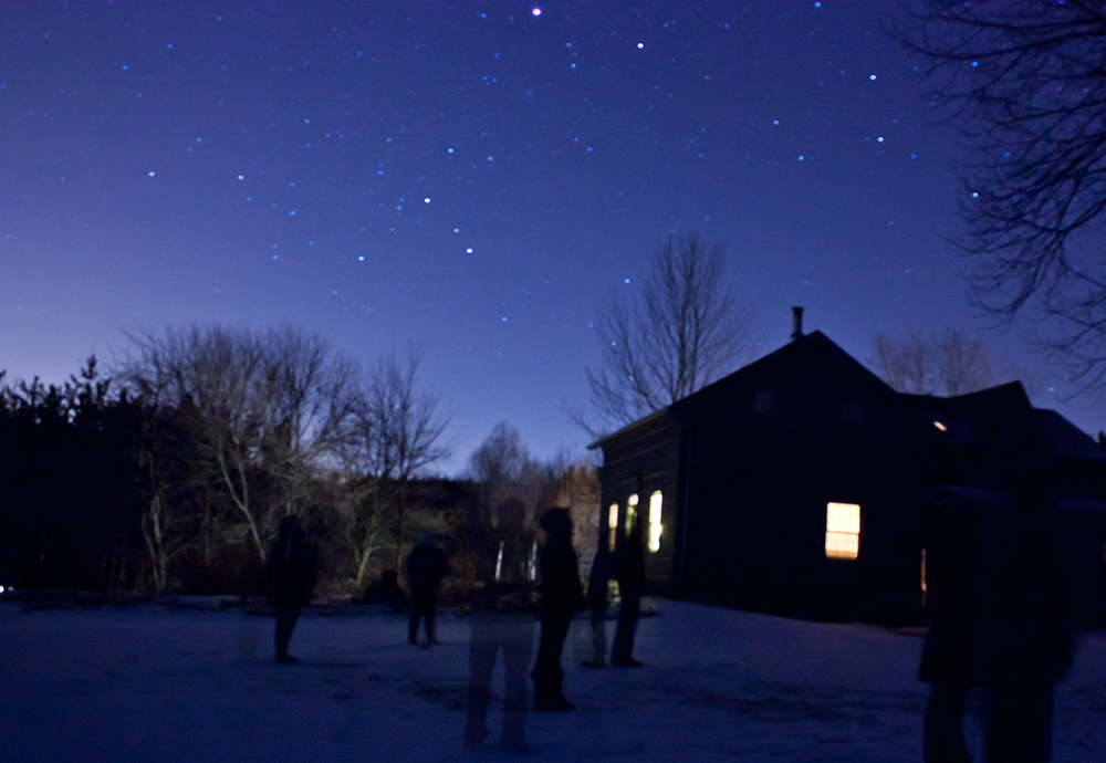 A photo of myself and friends stargazing one night outside of a similar lodge some years later.